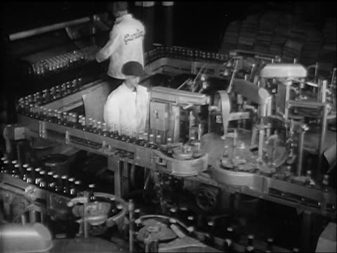 B/W 1933 high angle two men watching bottles of beer moving on conveyor in factory