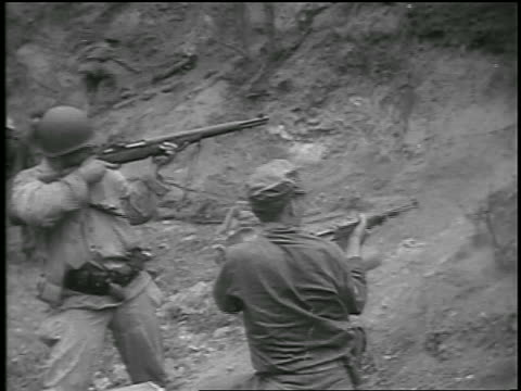 stockvideo's en b-roll-footage met b/w 1950 high angle two soldiers shooting rifles on hill / korean war / newsreel - koreaanse oorlog