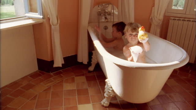 high angle two young boys playing in bathtub in bubble bath / boy playing w/rubber duck and looking at cam - bubble bath stock videos and b-roll footage