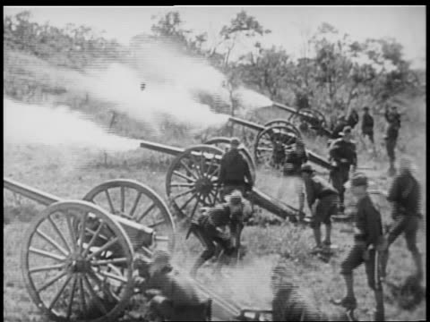 B/W 1898 REENACTMENT high angle U.S. soldiers shooting off cannons in Spanish-American war / documentary