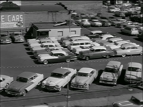 B/W 1957 high angle PAN of used car lot with salesmen