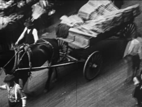 stockvideo's en b-roll-footage met b/w 1913 high angle pan vendor pulling cart loaded with brooms on street / lower east side, nyc - paardenkar