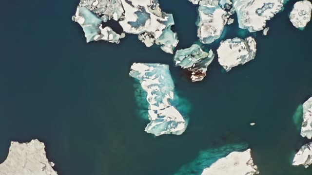 high angle video of glacier icebergs floating in lagoon in iceland - glacier stock videos & royalty-free footage