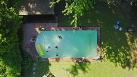vista video ad angolo alto della famiglia che si gode la piscina sul retro - swimming pool video stock e b–roll