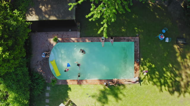 high angle video view of family enjoying backyard swimming pool - drone point of view stock videos & royalty-free footage