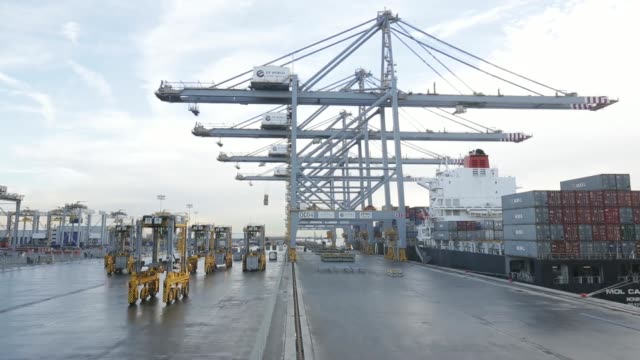 high angle view a kalmar straddle carrier moves along the dock side ahead of loading freight onto the mol caledon container ship operated by mitsui... - straddle carrier stock videos & royalty-free footage