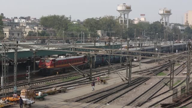 high angle view a train arrives at the new delhi railway station in new delhi trains sit on tracks at the new delhi railway station new delhi street... - delhi stock videos & royalty-free footage