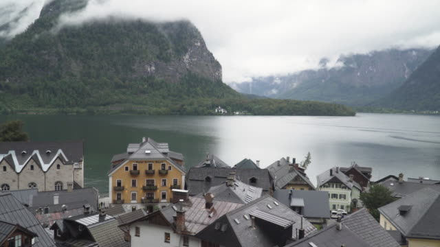 high angle view and panning: beautiful hallstatt lakefronts roof of a small village consisted of a church, residential building at mountain covering fog of raining day in summer. concept of an international landmark of austria. - village stock videos & royalty-free footage