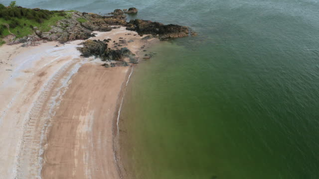 high angle view as a drone flies along a scottish beach on a summer day - johnfscott stock videos & royalty-free footage