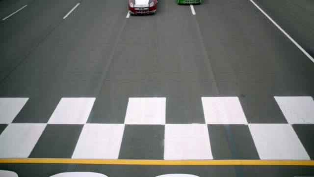 SLO MO. High angle view as three professional stock cars race across the finish line at motor speedway.