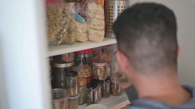 vidéos et rushes de vue à angle élevé mâle chinois asiatique récupérant la bouteille de nourriture de l'armoire d'étagère à la cuisine - placard