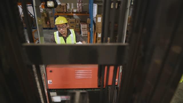 Hochwinkelansicht asiatischer chinesischer Lagerarbeiter, der Gabelstapler betreibt, der in der Industriefabrik arbeitet