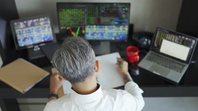 high angle view asian matured chinese man with gray hair working at home with stock exchange market multiple computer monitor monitoring market trend - finance stock videos & royalty-free footage