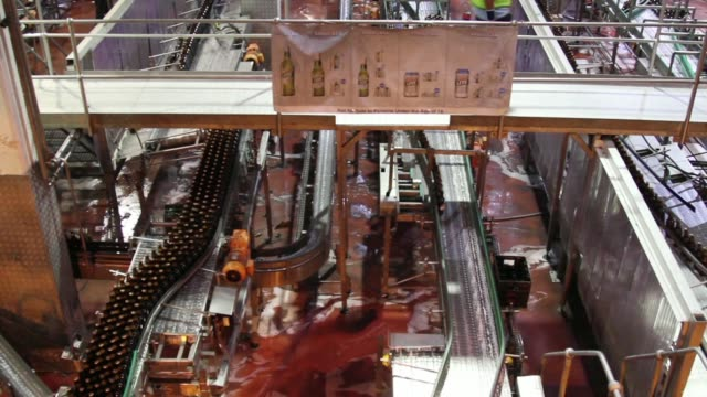 high angle view bottles move through labelling machine in the bottling plant at the sabmiller plc brewery in cape town south africa on friday march... - beer cap stock videos & royalty-free footage