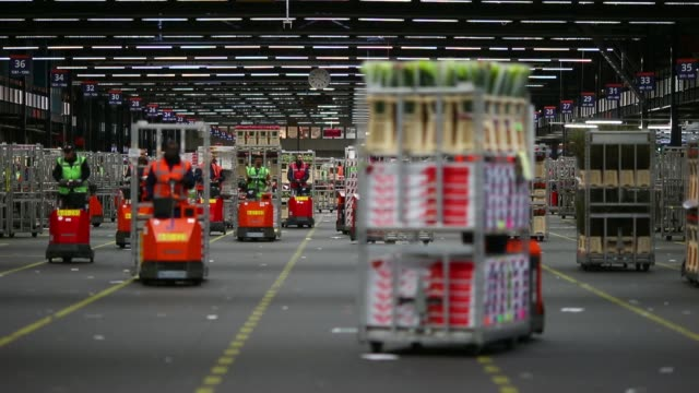 high angle view employees drive carts around warehouse as transport cages of flowers at floraholland the largest flower auction in the world in... - auction stock videos & royalty-free footage