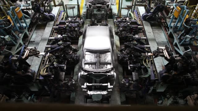 high angle view employees work on the chassis of a honda motor co amaze vehicle on the production line of the honda cars india ltd plant in greater... - ホンダ点の映像素材/bロール