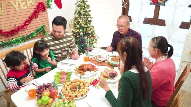 ้็hochwinkelansicht: vater bringt ein gegrilltes huhn mit, um den feiertag im dezember zu feiern, weihnachten in südostasiatischer mehrgenerationenfamilie, großeltern, enkel, die beim abendessen in einem mit weihnachtsbaum und ornament geschmückten  - 35 39 years stock-videos und b-roll-filmmaterial