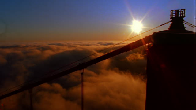 vídeos y material grabado en eventos de stock de high angle view from top golden gate bridge of sea of fog rolling over san francisco bay at sunset - imagen virada