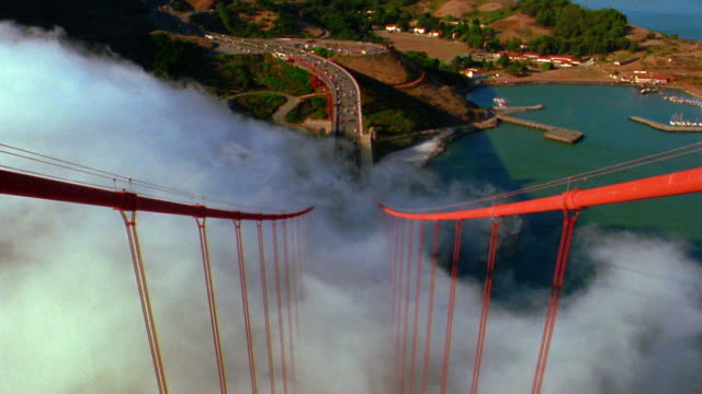 vídeos de stock, filmes e b-roll de high angle view from top golden gate bridge tower / fog moves thru suspension cables / traffic on road below - baía de são francisco