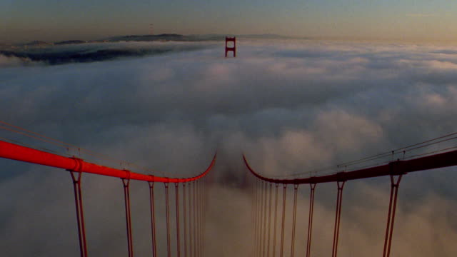 high angle view from top golden gate bridge tower of time lapse fog over bay and traffic on bridge / san francisco - san francisco bay stock videos and b-roll footage