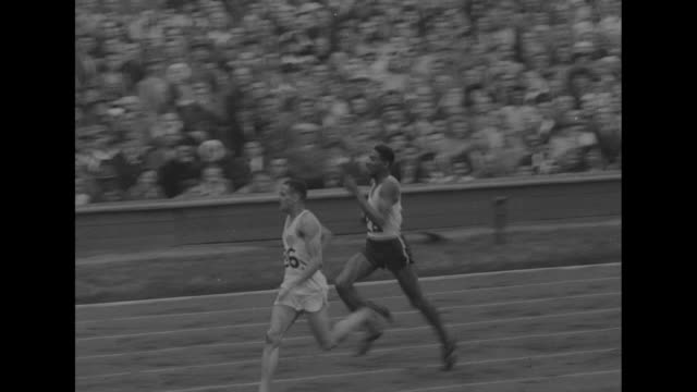 stockvideo's en b-roll-footage met high angle view infield of empire stadium during track and field events at summer olympics in london / crowd in grandstands / 800-meter race starts /... - moving past