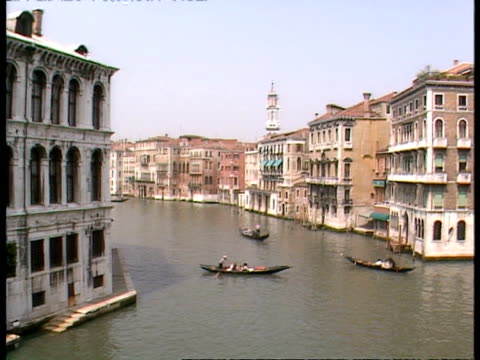 vídeos de stock e filmes b-roll de wa high angle view of 3 gondolas on large canal with old venetian buildings on either side, venice - embarcação comercial