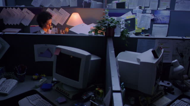 high angle view of 4 cubicles in dark office / one with lamp on + woman working at computer + drinking coffee