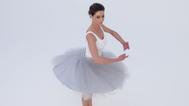 high angle view of a classical ballet dancer dancing against a white backdrop. - anmut stock-videos und b-roll-filmmaterial