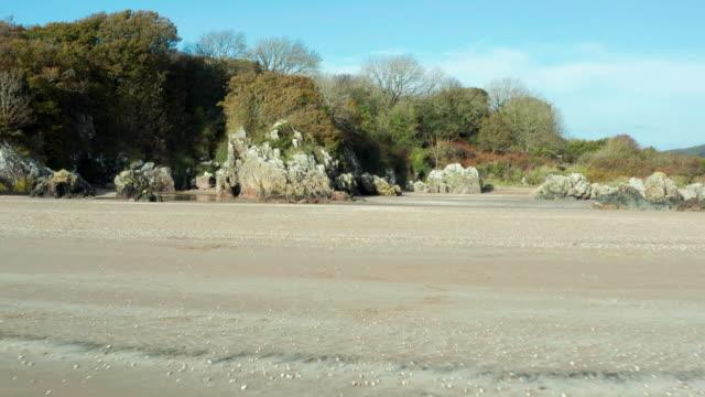 vídeos y material grabado en eventos de stock de vista de alto ángulo de una playa rocosa desierta en marea baja en el suroeste de escocia - brightly lit