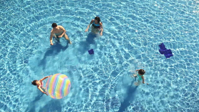 High angle view of a family playing with a ball in a swimming pool