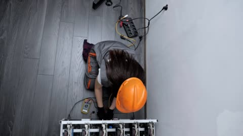 vídeos de stock e filmes b-roll de high angle view of a female electrician working on an it item, engineering, measuring electrical resistance, professional it support, technology, stem, experienced professional - generation z