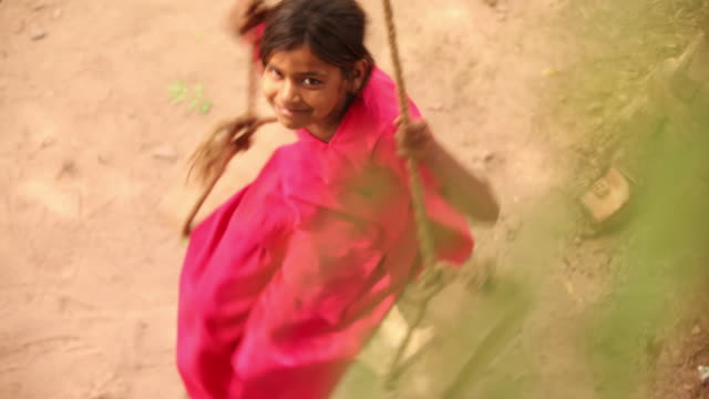 high angle view of a girl spinning in a swing, faridabad, haryana, india - 揺れる点の映像素材/bロール