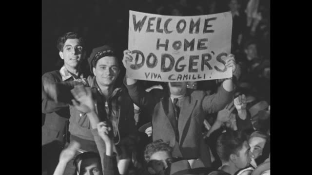 high angle view of a large crowd at night / airplane òflagshipó taxis on tarmac / man in crowd òwelcome home dodgers viva camillió / brooklyn dodgers... - newspaper page stock videos and b-roll footage