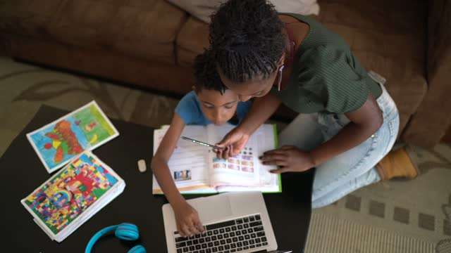 high angle view of a mother helping son using laptop on homeschooling - responsibility stock videos & royalty-free footage