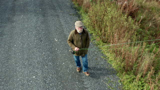 high angle view of a senior man on a forest road beside a loch with a fly fishing rod - galloway scotland stock videos & royalty-free footage