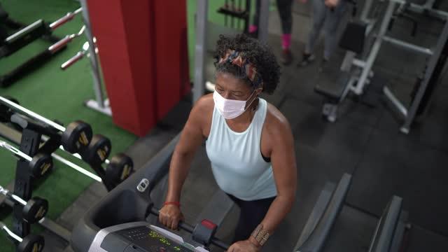 vídeos de stock, filmes e b-roll de visão de ângulo alto de uma mulher idosa na esteira em uma academia - usando máscara facial - exercício cardiovascular