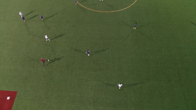 vidéos et rushes de vue grand angle d'une équipe de football, passer le ballon vers le haut le champ - stratégie