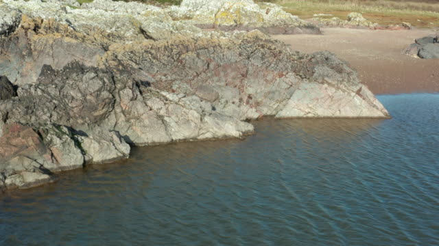 スコットランド南西部の干潮時のビーチの潮汐プールの高角図 - brightly lit点の映像素材/bロール