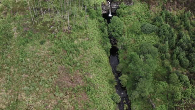 vidéos et rushes de vue d'angle élevé d'une chute d'eau en cascade dans la petite rivière lente coulant dans un sud-ouest rural éloigné de l'ecosse - remote location