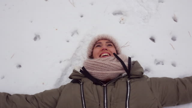 high angle view of a woman lying in the snow and making snow angel - mitten stock videos and b-roll footage