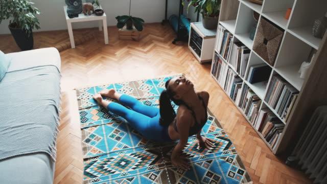 vídeos y material grabado en eventos de stock de vista de ángulo alto de una mujer joven que practica la pose de perro orientada hacia arriba en casa - postura