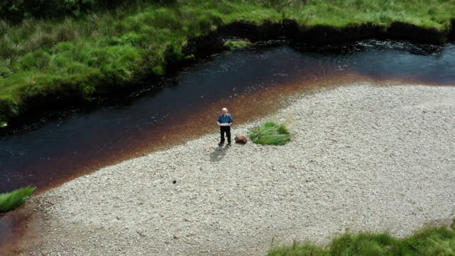 high angle view of an active senior man looking at a map while standing at the side of a small river in rural south west scotland on a summer day - galloway scotland stock videos & royalty-free footage