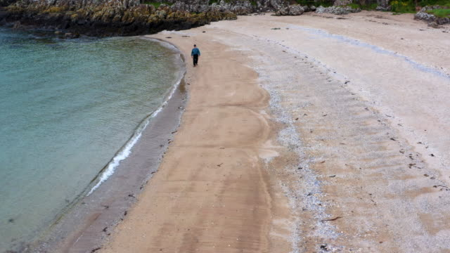 high angle view of an active senior man walking along a scottish beach on a summer day - johnfscott stock videos & royalty-free footage