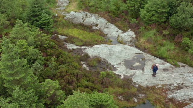 high angle view of an active senior man walking on a large granite outcrop in a remote part of rural south west scotland - johnfscott stock videos & royalty-free footage