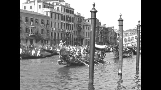 high angle view of an innumerable collection of vintage gondolas with the rialto bridge in the distance / an ornate baroque boat with eight rowers... - 1920 1929 video stock e b–roll