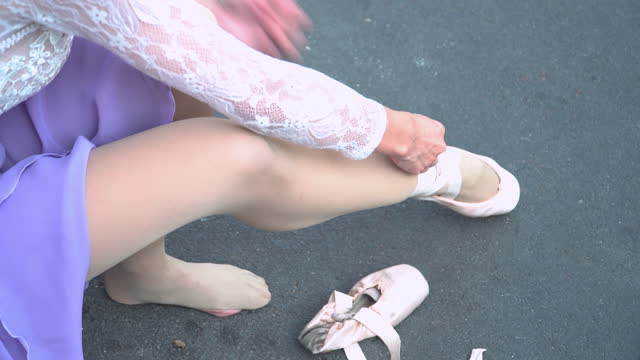 high angle view of asian beautiful ballet dancer in white and violet color practicing prepare ballet shoe on a local street in a cityscape, bangkok, thailand. concept of the active young woman at weekend activities. - ballet shoe stock videos & royalty-free footage
