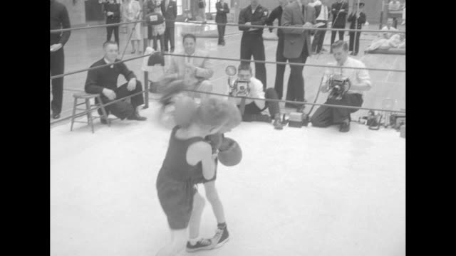 High angle view of Bart Connolly Robert Healy in boxing ring / boy knocked out gets up immediately / parents man in naval uniform / view of fight...
