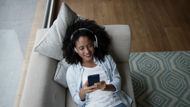 high angle view of black woman relaxing on couch listening music with headphones and using smartphone looking very happy - listening stock videos & royalty-free footage