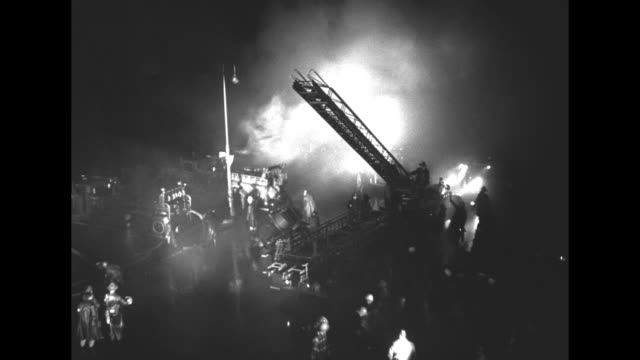 high angle view of broken water main at night / smoke pours across scene lit with spotlights / ladders from firetrucks raised high in air with men... - 大量破壊兵器点の映像素材/bロール