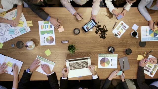 high angle view of business development team in strategy meeting - conference table stock videos & royalty-free footage